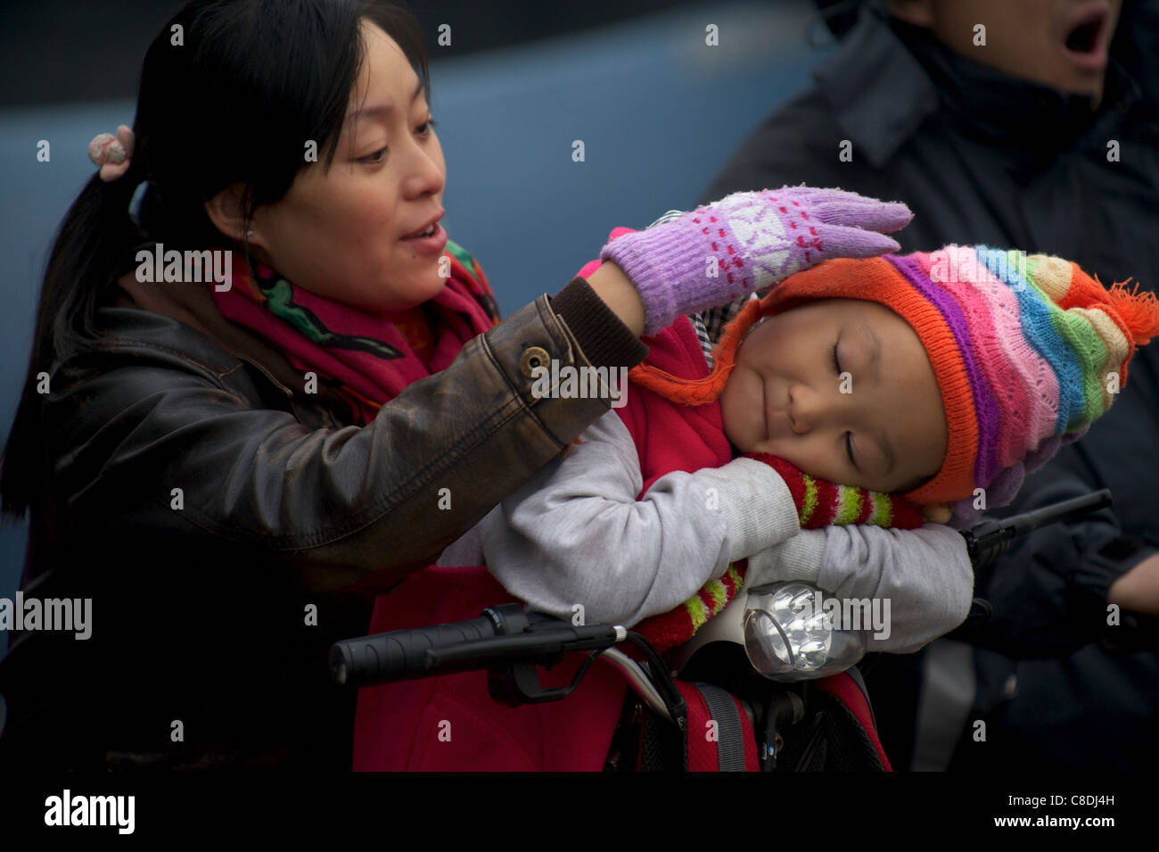 A Chinese mother touches her baby on an electric bicycle in Beijing, China. 20-Oct-2011 - Stock Image