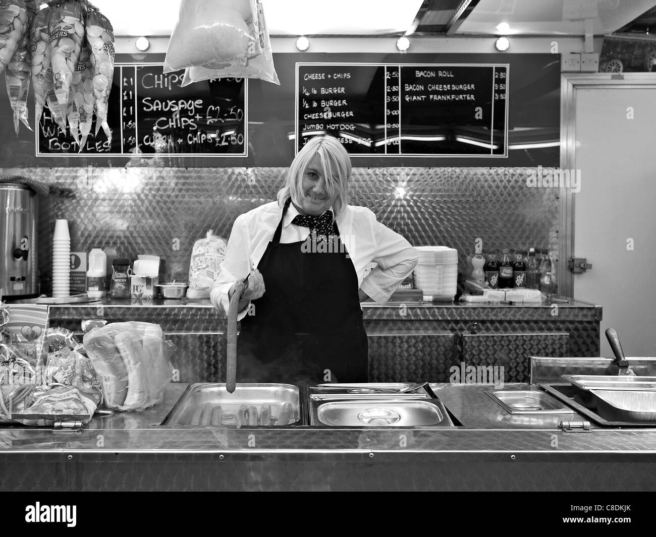 Fast food stall worker holds up a large Frankfurter sausage England UK Black and white photography - Stock Image