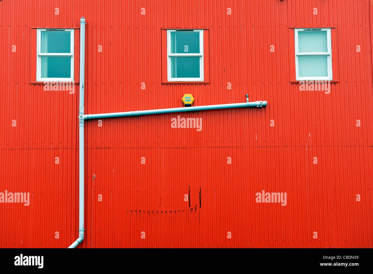 A drainpipe on the side of a red corrugated iron building in Lerwick, Shetland Islands, Scotland. - Stock Image