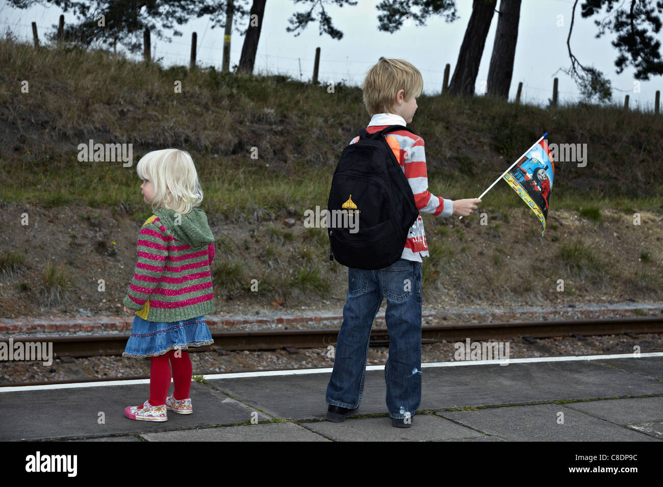 Older brother and younger sister wait patiently at the station platform for the arrival of Thomas the Tank Engine. - Stock Image