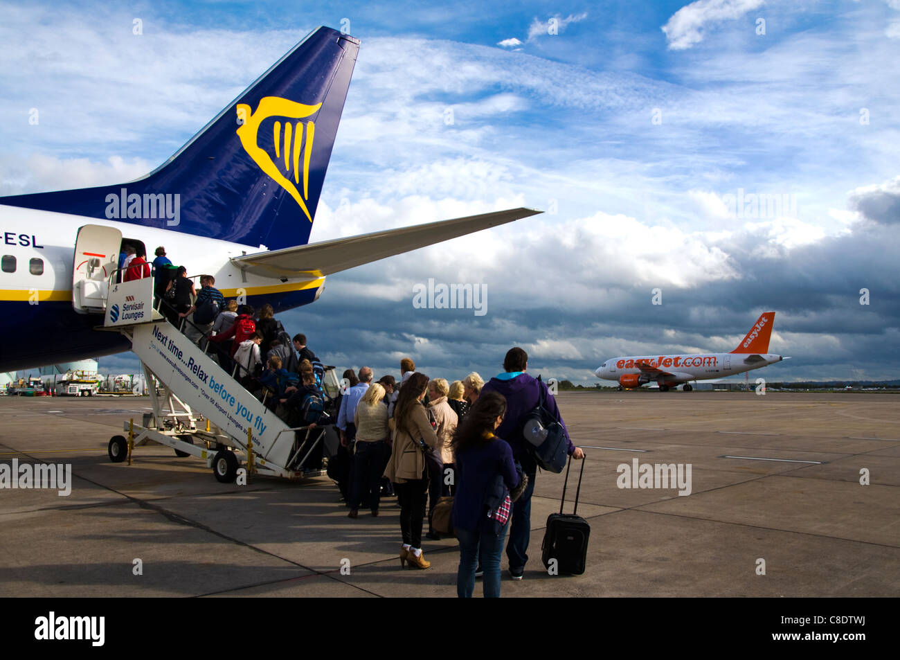 Passengers queue to board a Ryanair Boeing 737-800 plane as an Easyjet airplane lands - Stock Image