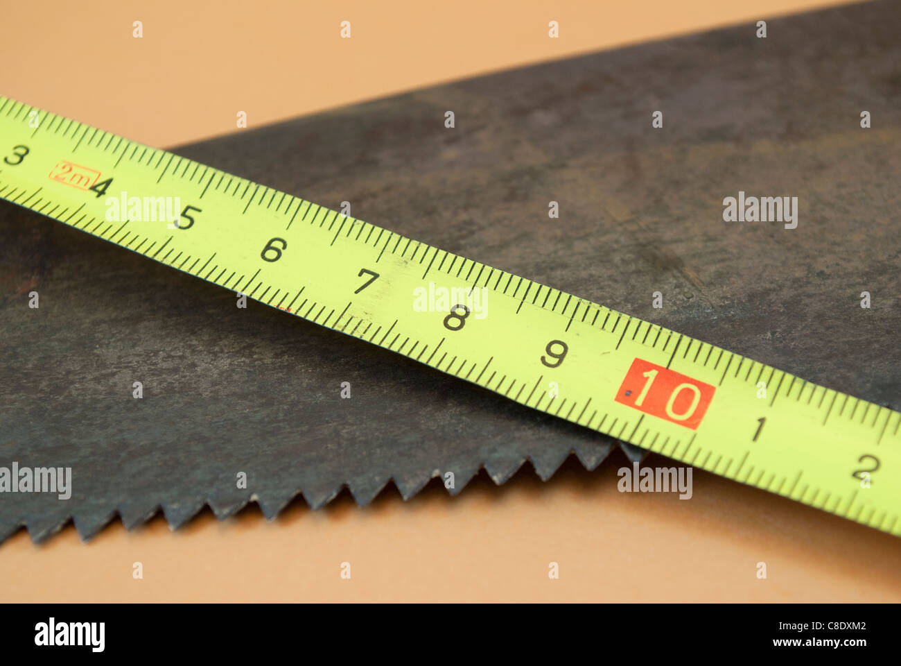 meter and hand saw - Stock Image