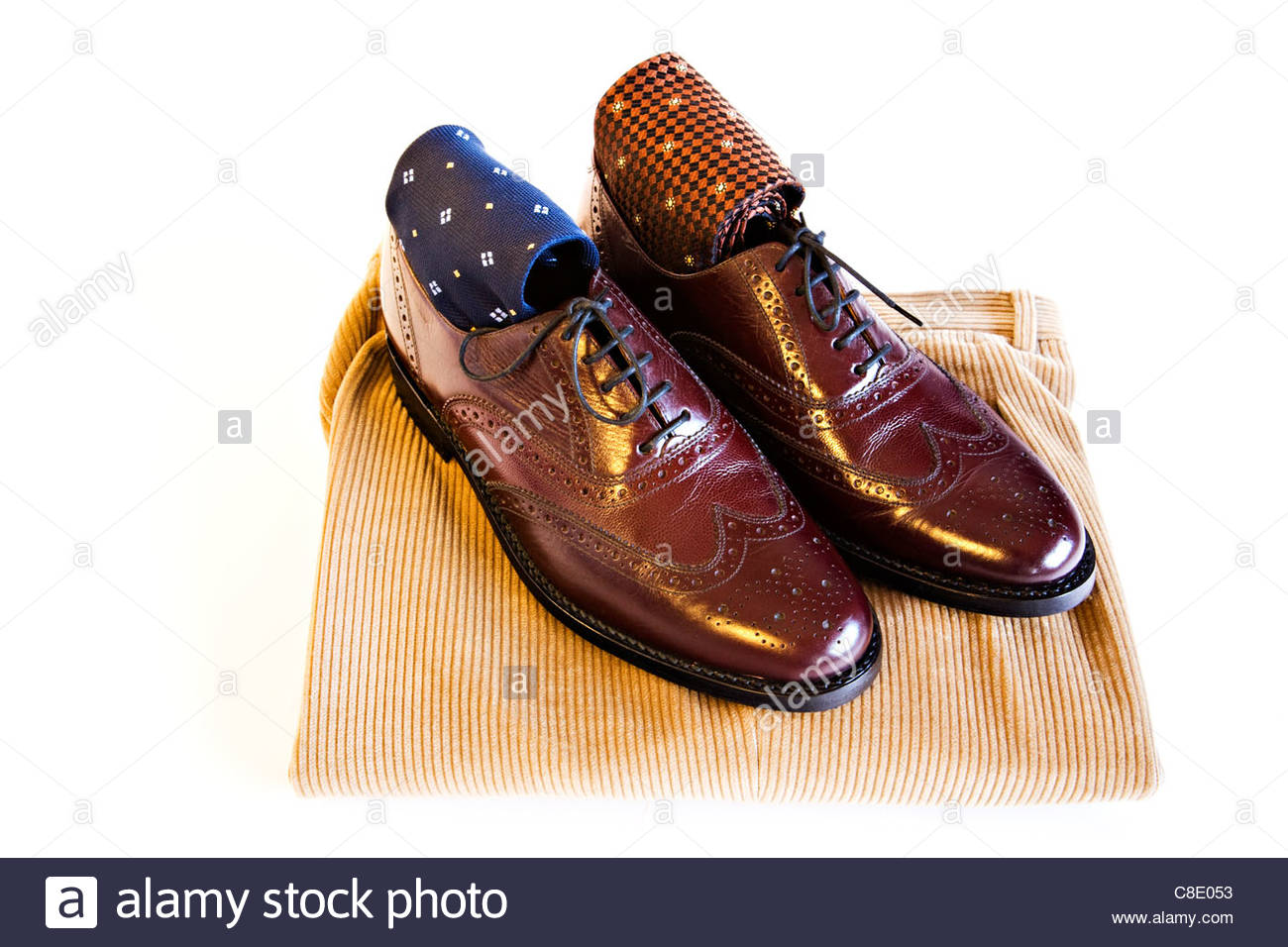 Men's brown polished leather lace up shoes with ties and trousers on white background - Stock Image