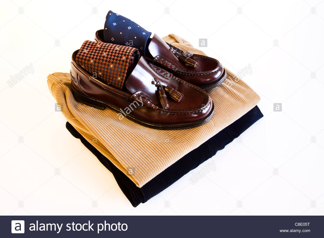 Men's brown polished leather shoes with ties and trousers on white background - Stock Image