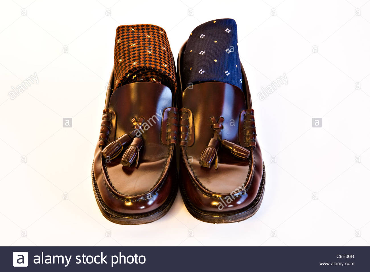 Men's brown polished leather shoes with ties on white background - Stock Image