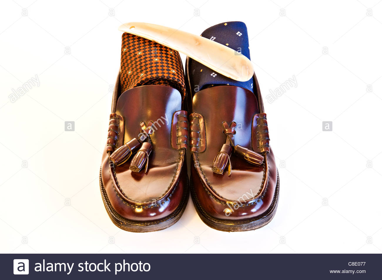Men's brown leather shoes with ties and shoe horn on white background - Stock Image