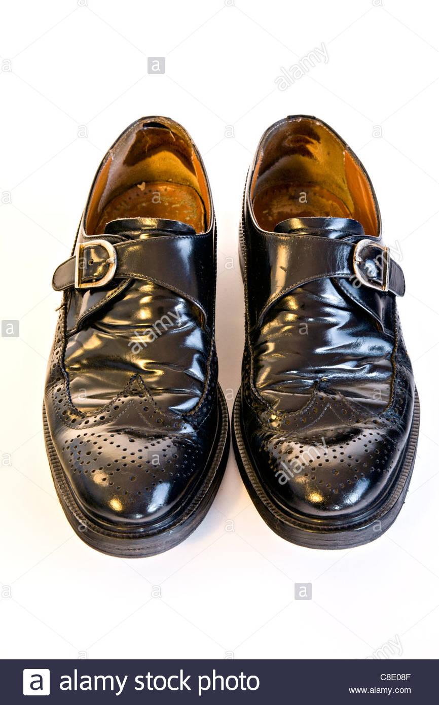 Well worn Men's black leather shoes on white background - Stock Image
