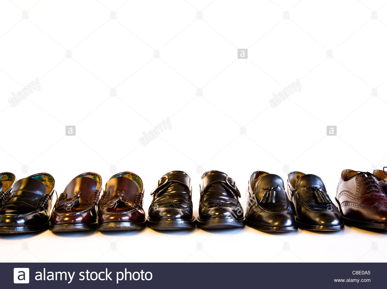 Selection of Men's well worn black and brown leather shoes on white background - Stock Image