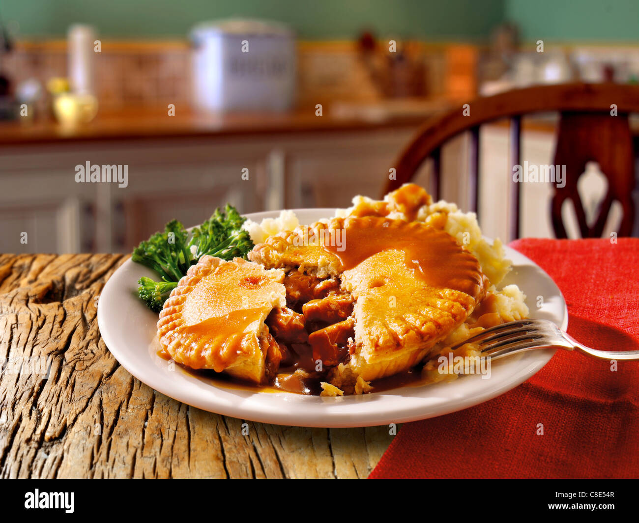 Traditional British beef pastry pie served on a white plate on a table in a  traditional kitchen setting ready to Stock Photo
