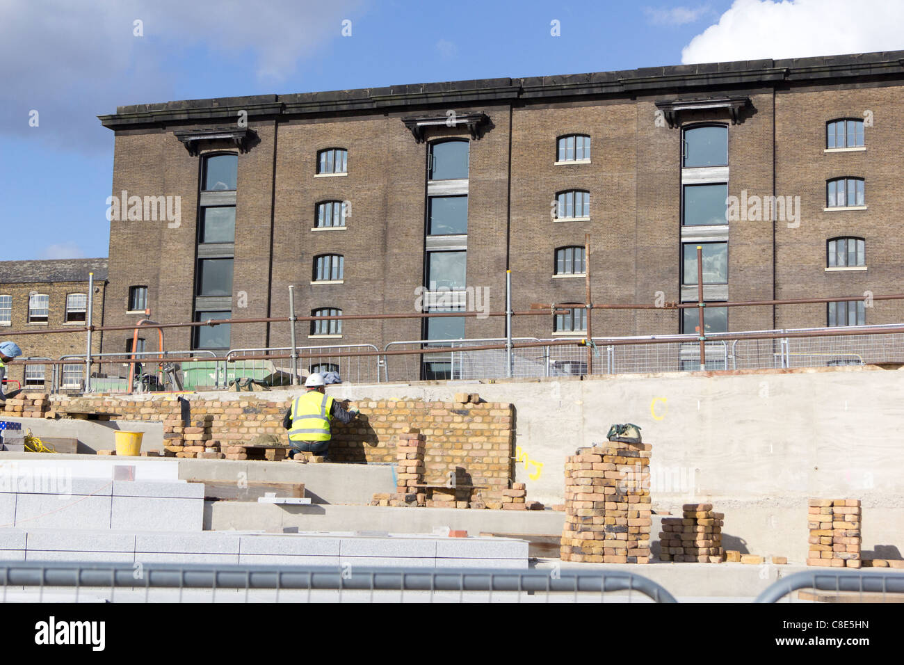 Hard landscaping work being carried out on the banks of the Regents Canal at the Kings Cross development, - Stock Image