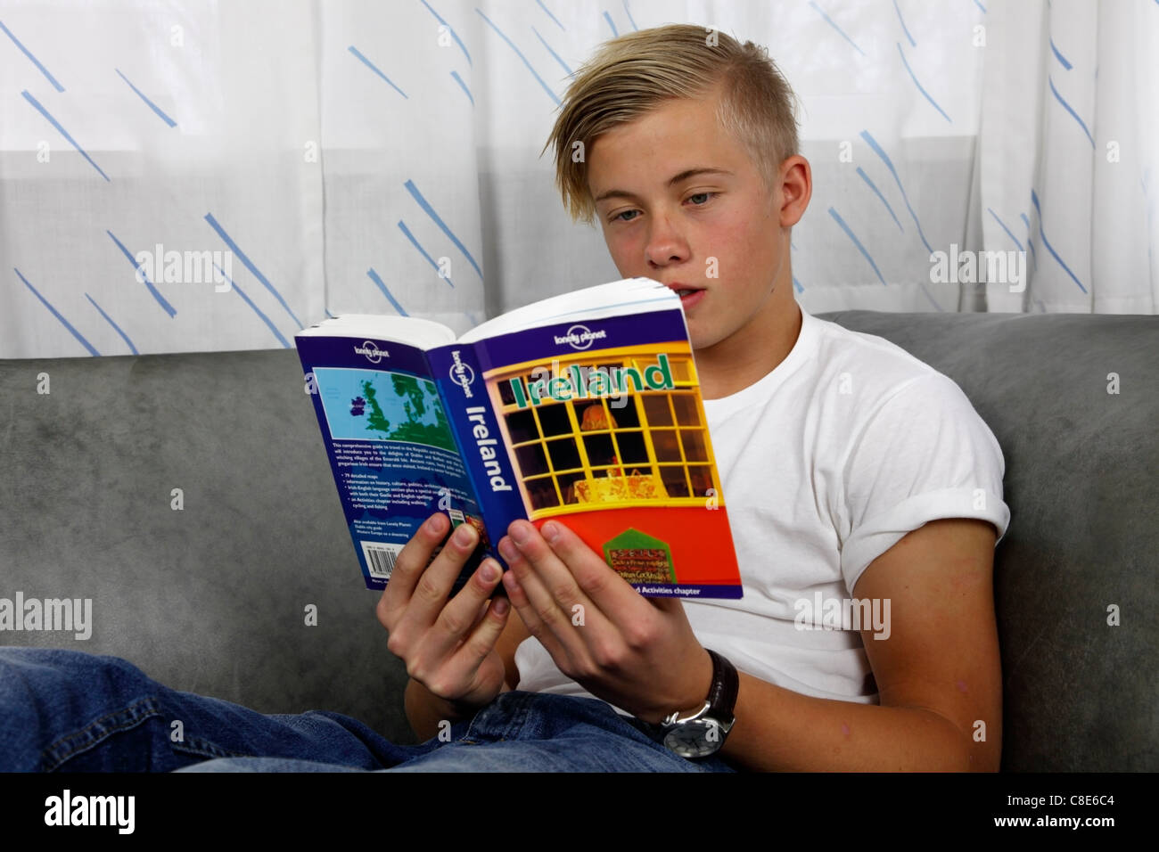 Relaxed Danish, male teenager reading the Lonely Planet guide to Ireland. - Stock Image