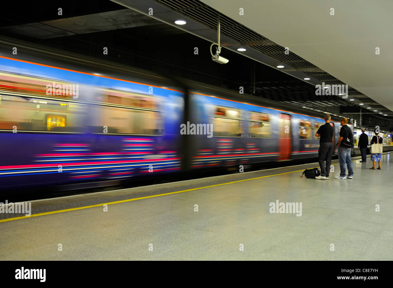 Motion blur of moving train & static passengers on platform at St Pancras International railway station for - Stock Image