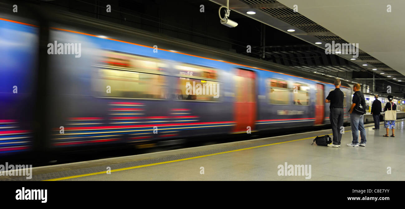 Motion blur of moving train & passengers on platform at St Pancras International low level railway station on - Stock Image
