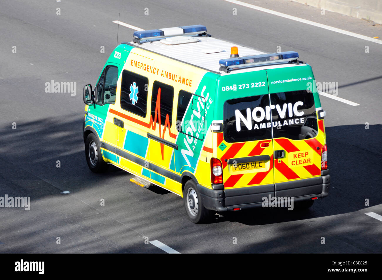 Close up of Norvic private sector emergency health care ambulance business driving along M25 motorway Essex England - Stock Image