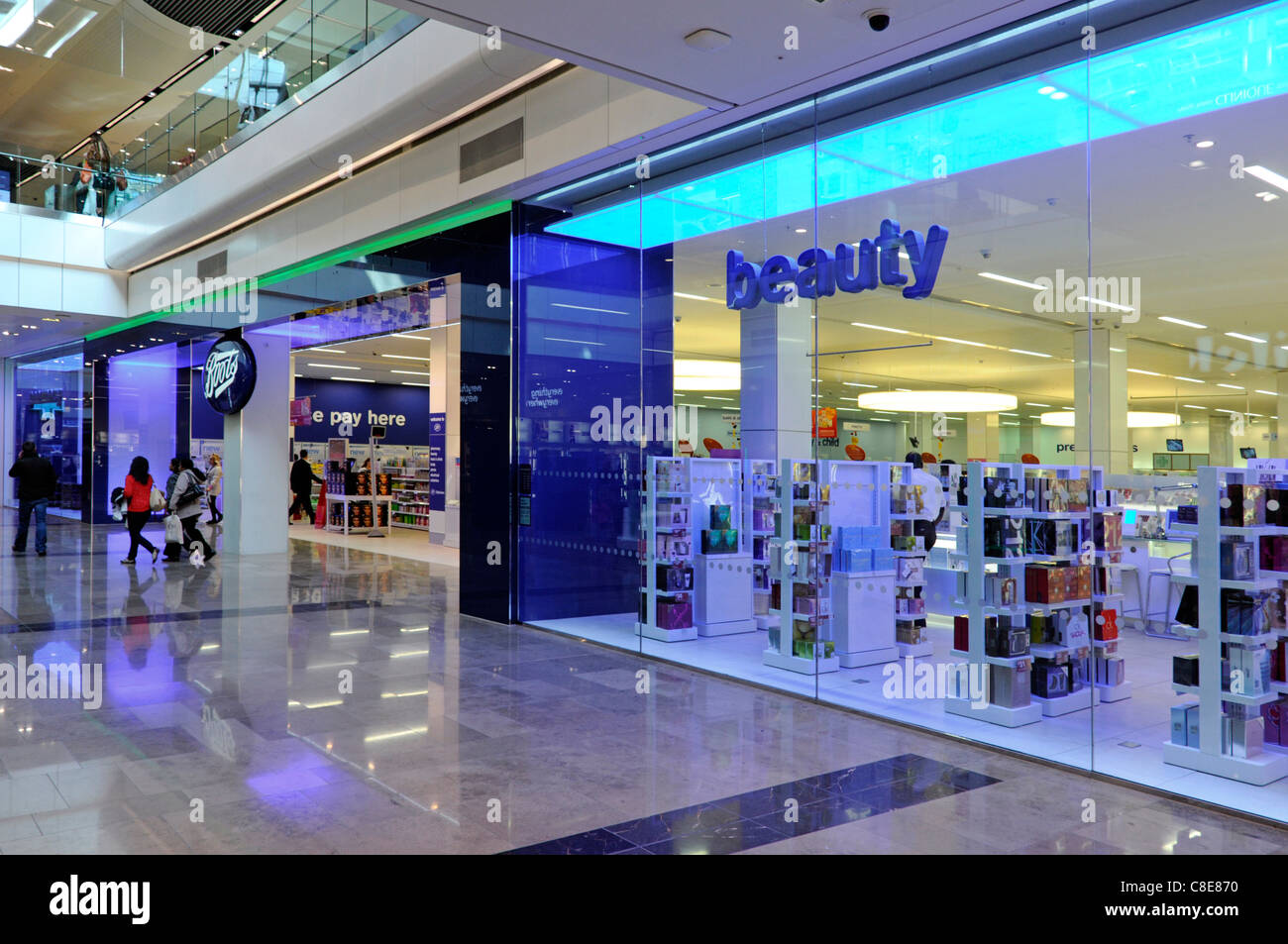 People in Boots pharmacy chemist beauty shop front & window in Westfield shopping centre mall in Stratford City - Stock Image