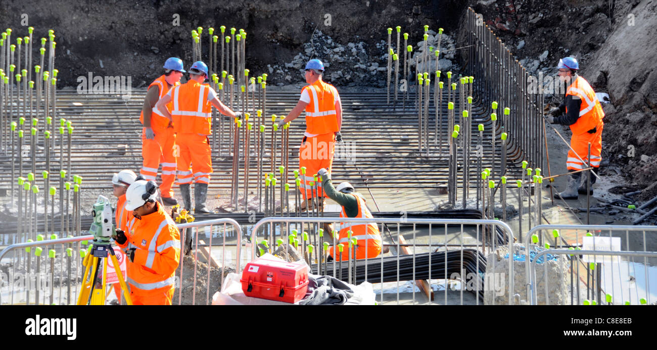 Health & safety construction building site hard hat workers steel reinforcement rods with yellow safety caps to Stock Photo