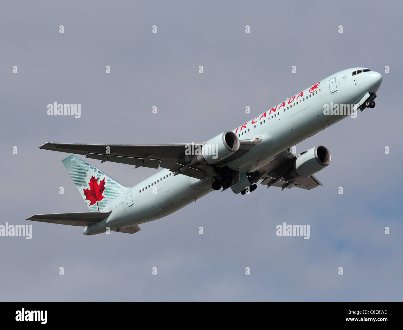 Air Canada Boeing 767-300ER passenger jet plane climbing on takeoff and retracting its undercarriage - Stock Image