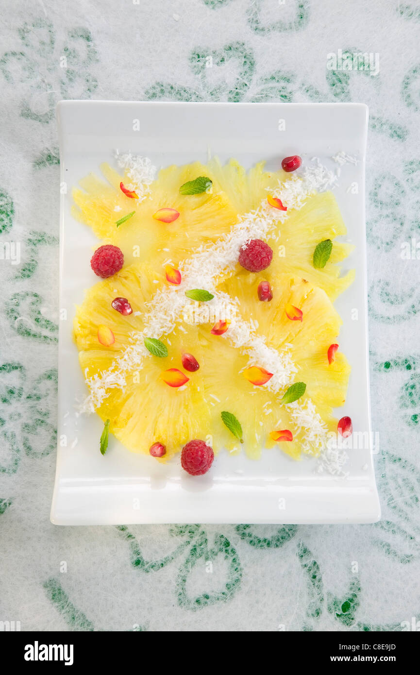 Pineapple Carpaccio with coconut,pomegrante seeds,raspberries and mint - Stock Image