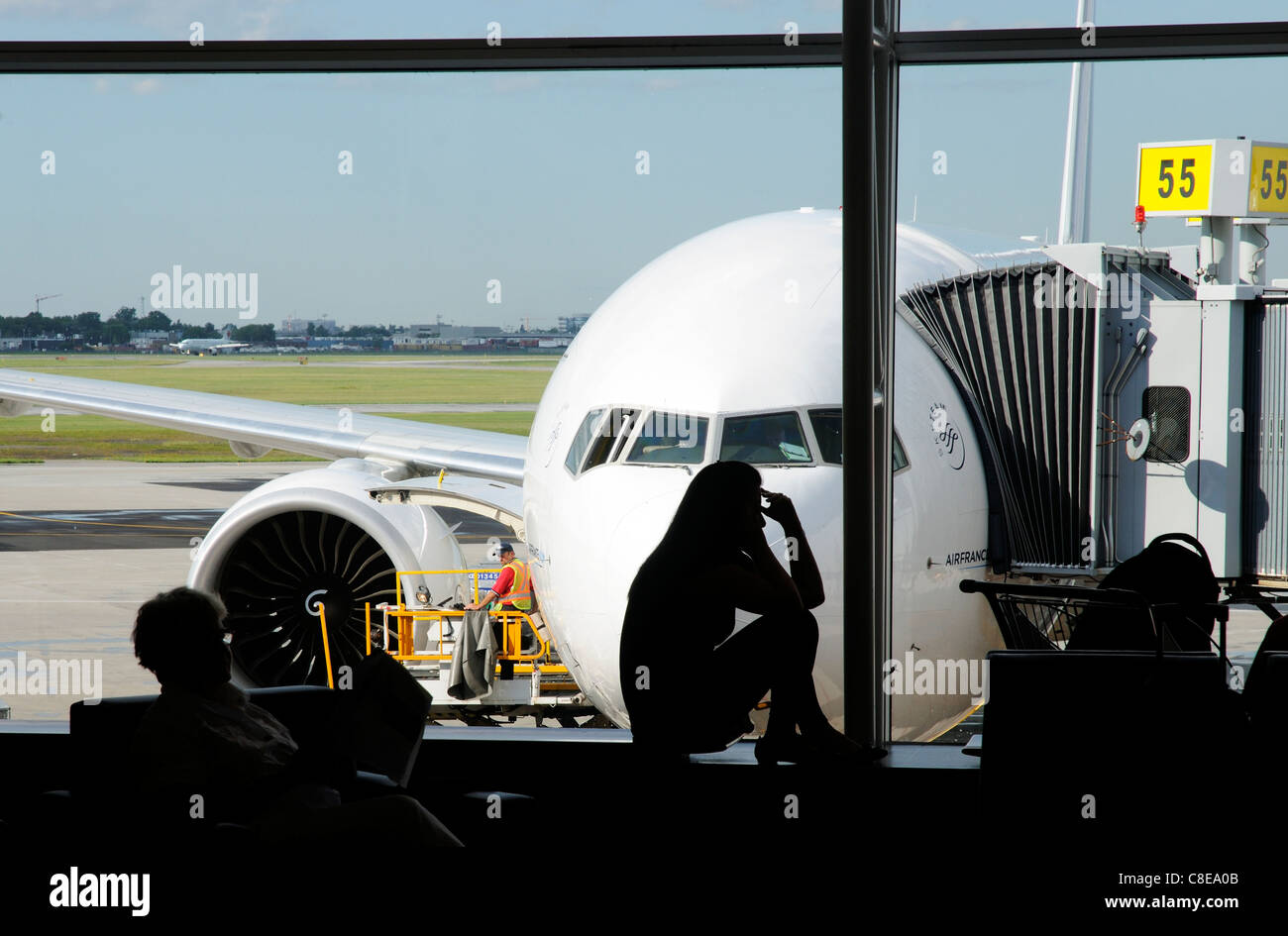 A young woman on a mobile phone in silhouette in an airport departure lounge window with a plane behind - Stock Image