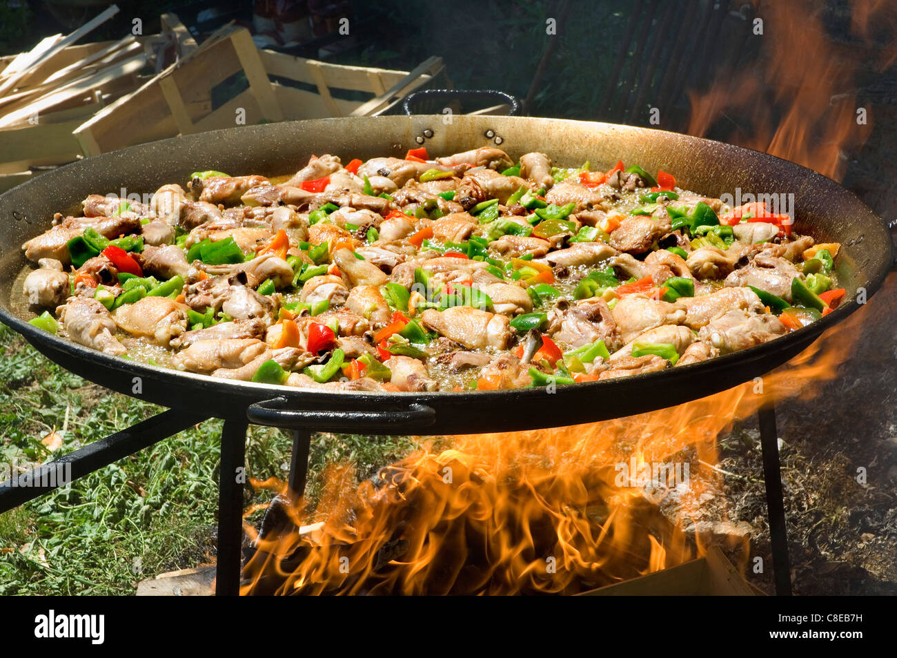 Cooking paëlla in a large dish on an open wood fire - Stock Image