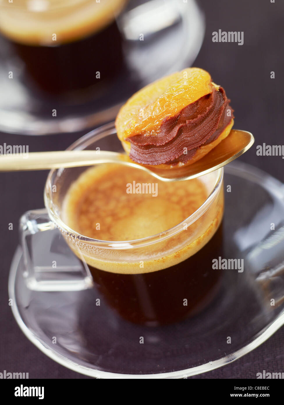 Dried apricot with chocolate filling and a cup of coffee - Stock Image