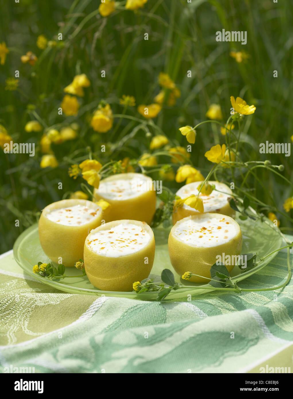 Lemon yoghurts serve in lemons - Stock Image