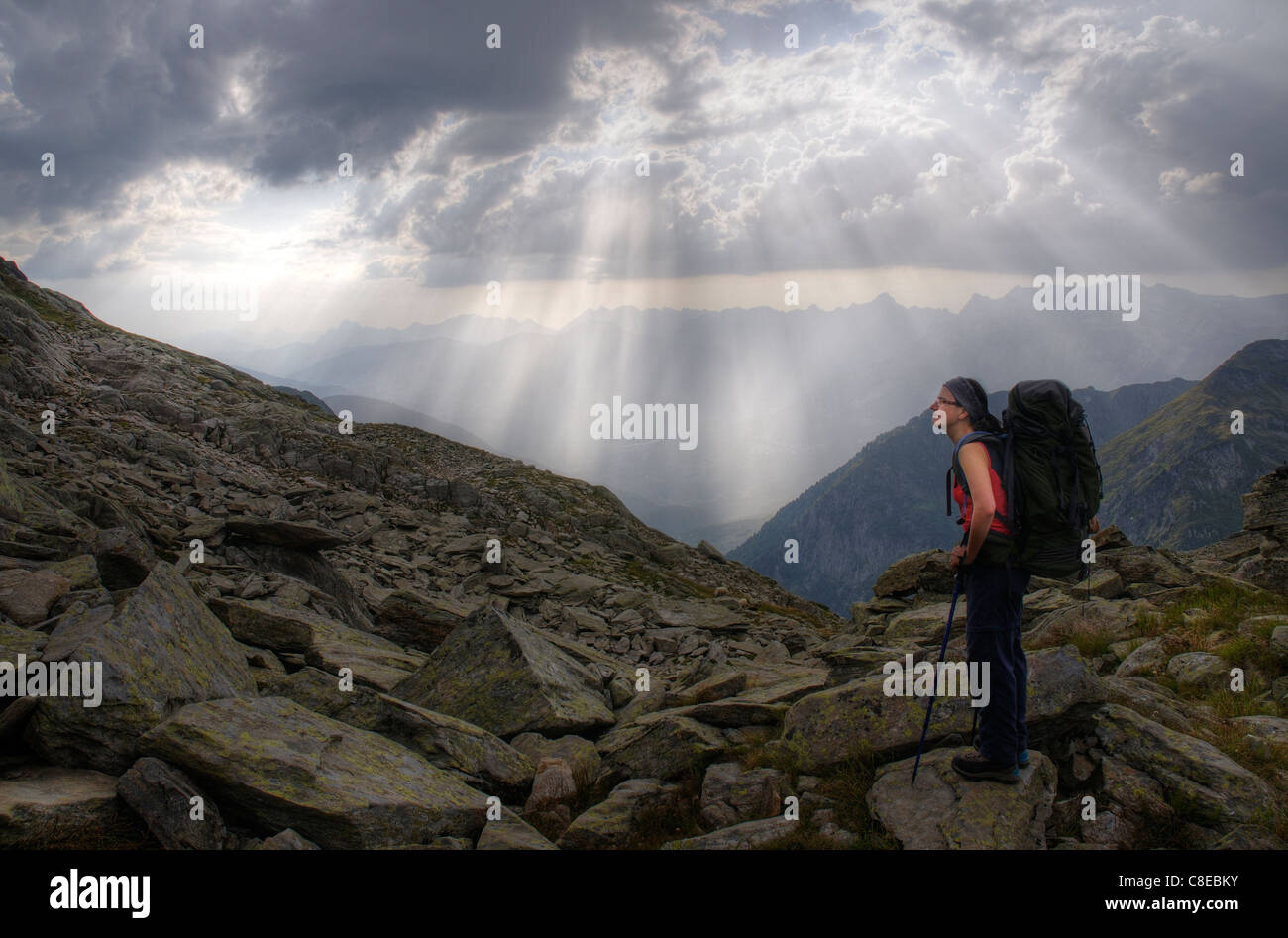 A mountain walker pauses with dramatic sun rays falling from the clouds - Stock Image