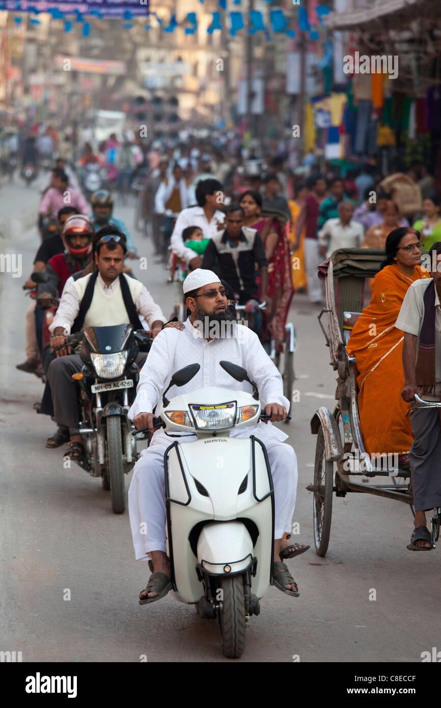 Muslim man wearing topi cap and white outfit driving motor scooter in street scene in city of Varanasi, Benares, - Stock Image