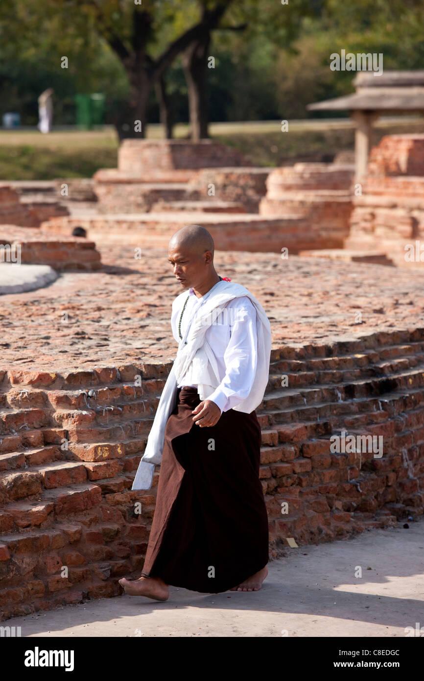Buddhist monk praying as he walks around Dharmarajika Stupa at Sarnath ruins near Varanasi, Benares, Northern India Stock Photo
