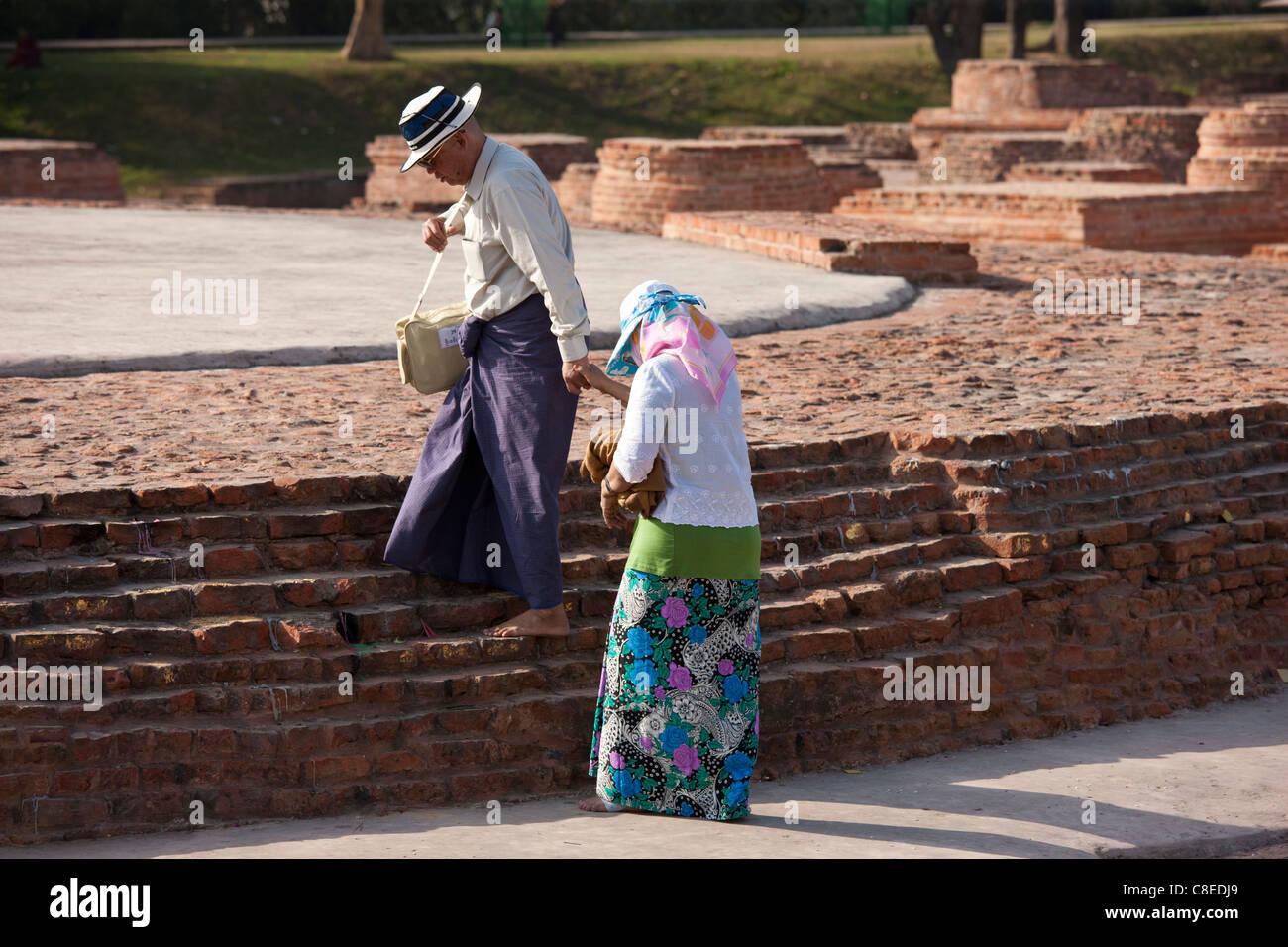 Japanese tourist couple at Dharmarajika Stupa at Sarnath ruins near Varanasi, Benares, Northern India - Stock Image