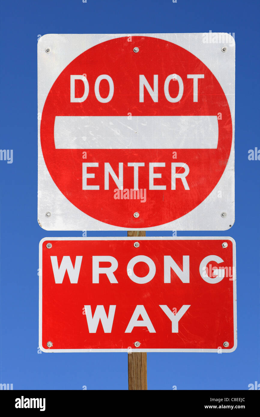do not enter wrong way red and white road sign on blue sky background - Stock Image