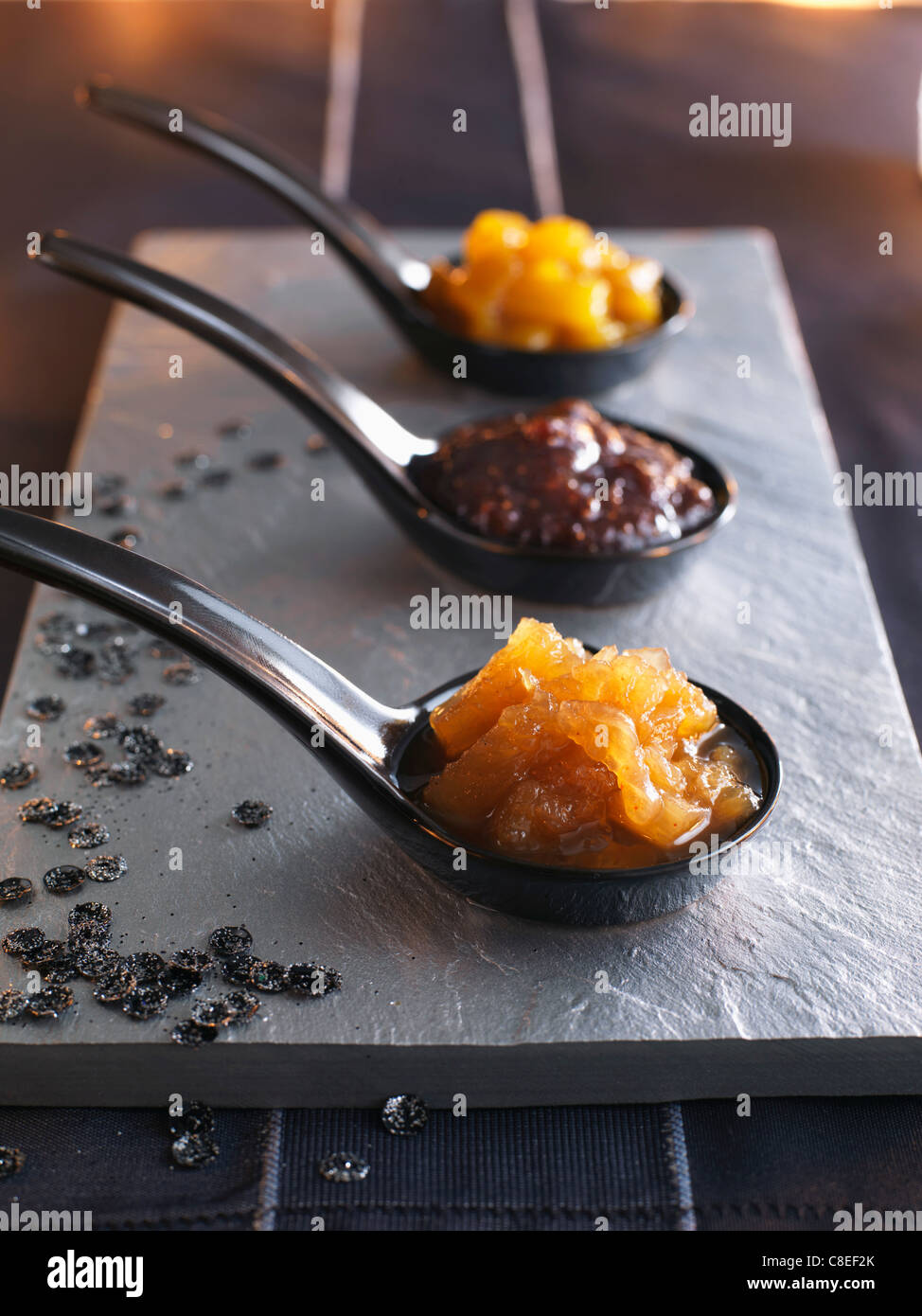 Spoons of different varieties of chutneys - Stock Image