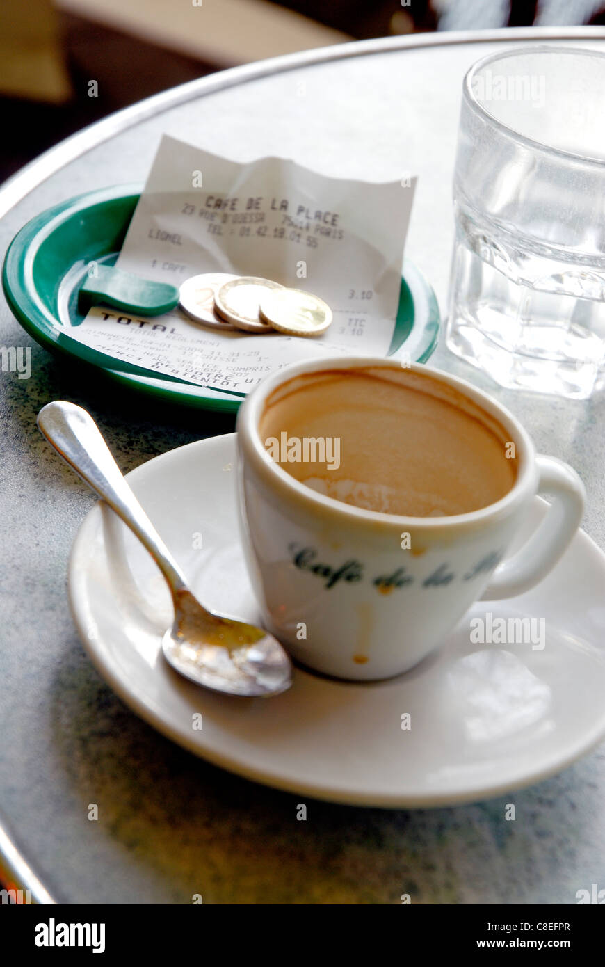 Finished coffee cup,bill and change at the terrace of a Bistrot - Stock Image