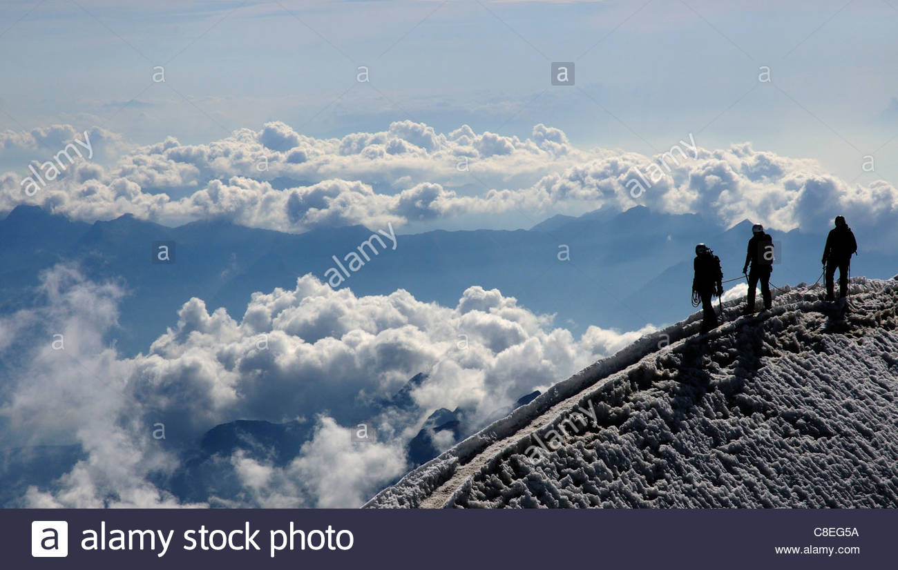 Climbers on the summit of a mountain in the Swiss Alps - Stock Image