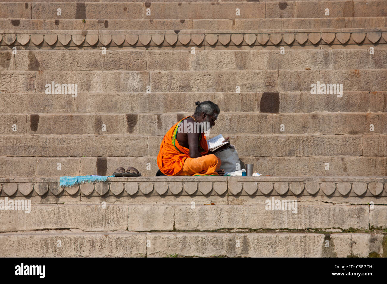 Hindu Sadhu holy man with traditional robe reads on steps of the Ghats in holy city of Varanasi, Benares, Northern Stock Photo
