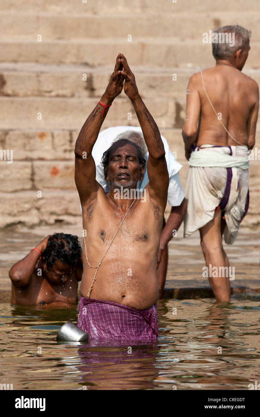 5de11a02309 Indian Hindu man bathing and praying in the River Ganges by Kshameshwar  Ghat in holy city of Varanasi, India