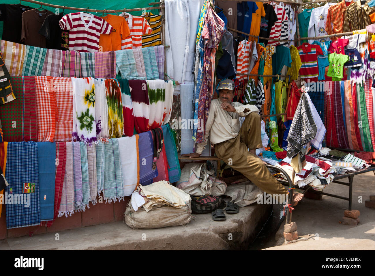 Stallholder selling clothes and sari fabrics and other textiles at Varanasi, Northern India - Stock Image