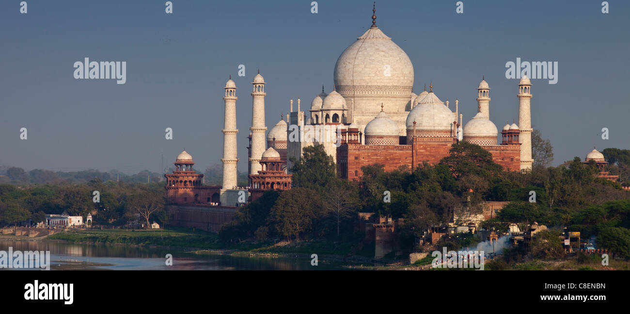 Hindu traditional funeral pyre cremation by The Taj Mahal and Yamuna River at sunset from Agra Fort, Khas Mahal - Stock Image