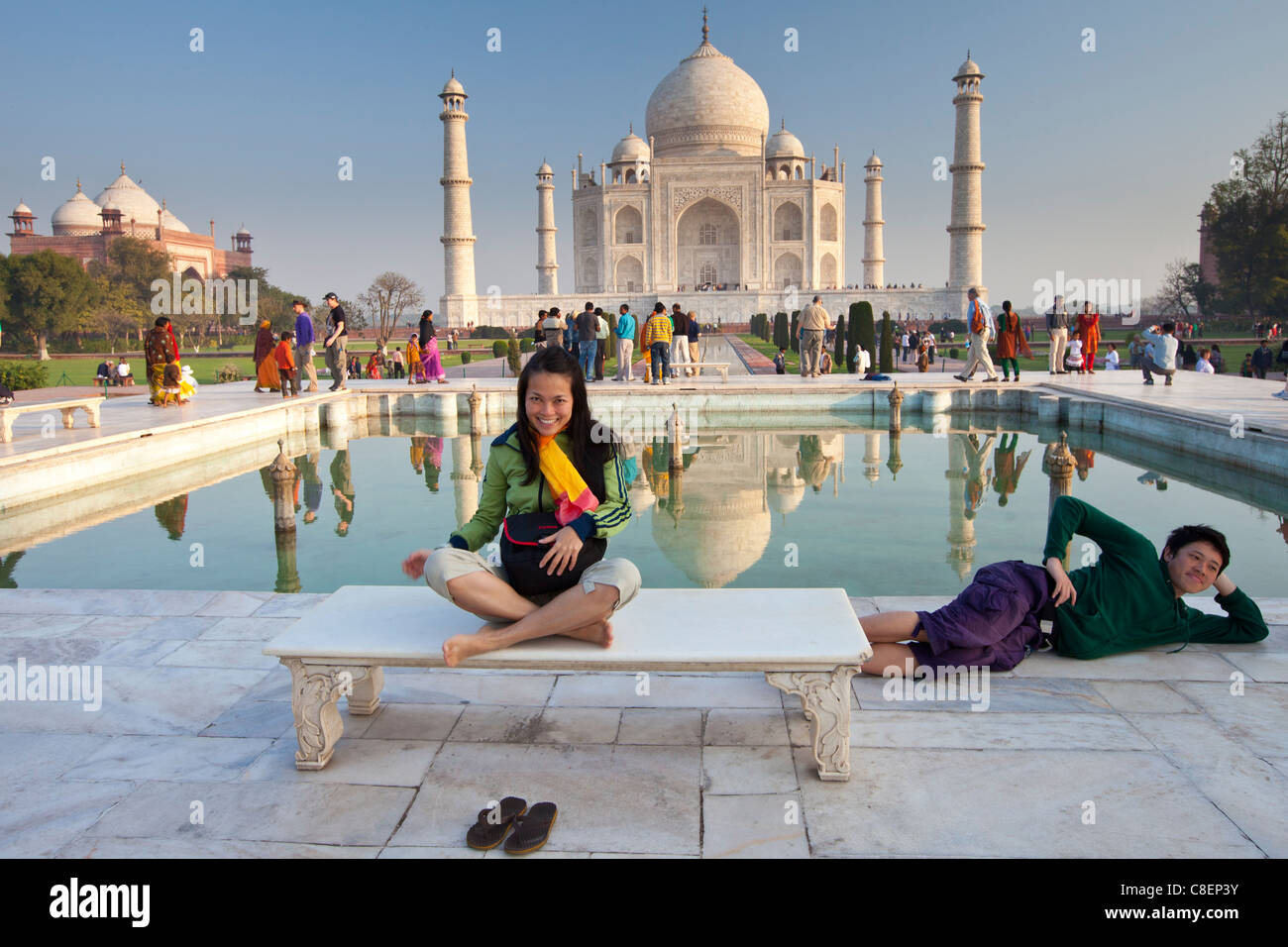 Tourists sit on Diana bench at The Taj Mahal mausoleum southern view with reflecting pool, Uttar Pradesh, India - Stock Image
