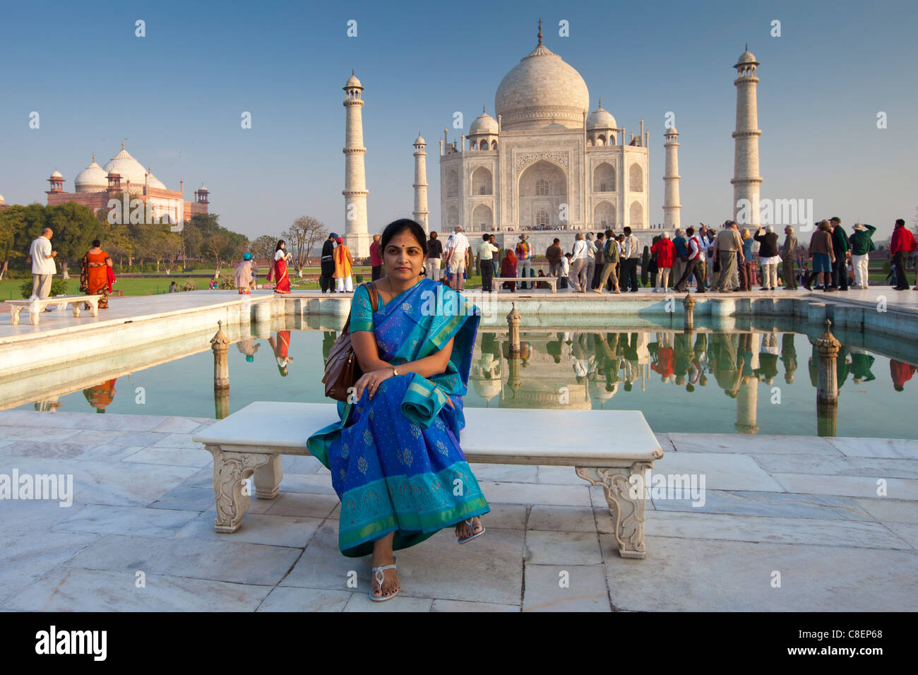 Indian tourist sits on Diana bench at The Taj Mahal mausoleum southern view with reflecting pool, Uttar Pradesh, - Stock Image
