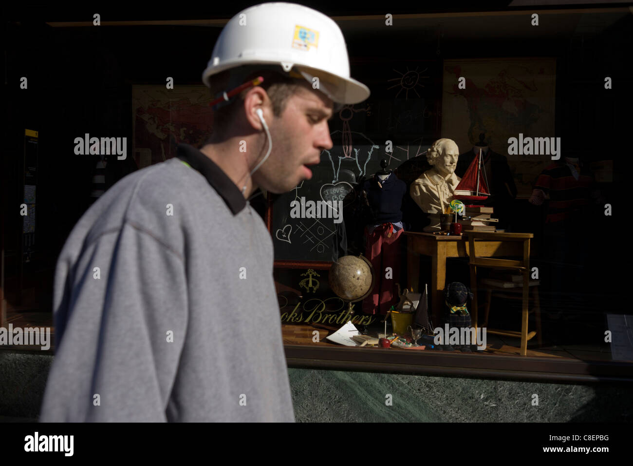 A manual labourer passes-by the a head of English playright William Shakespeare whose bust is sunlit in a London - Stock Image