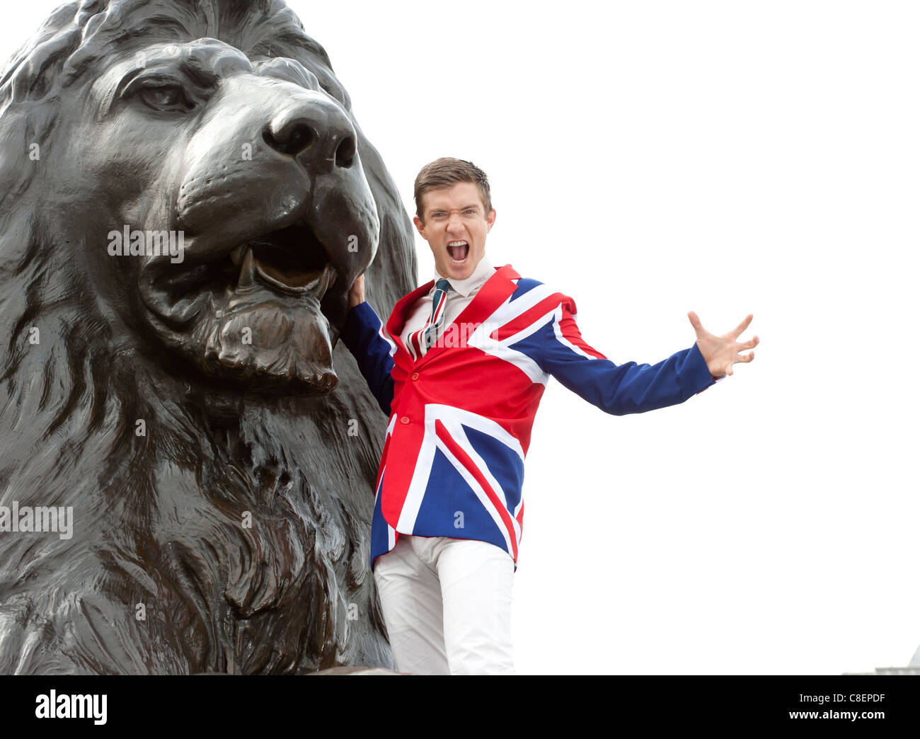 Young man wearing Union Flag jacket roaring next to the lion statue,  Trafalgar Square, London, England - Stock Image