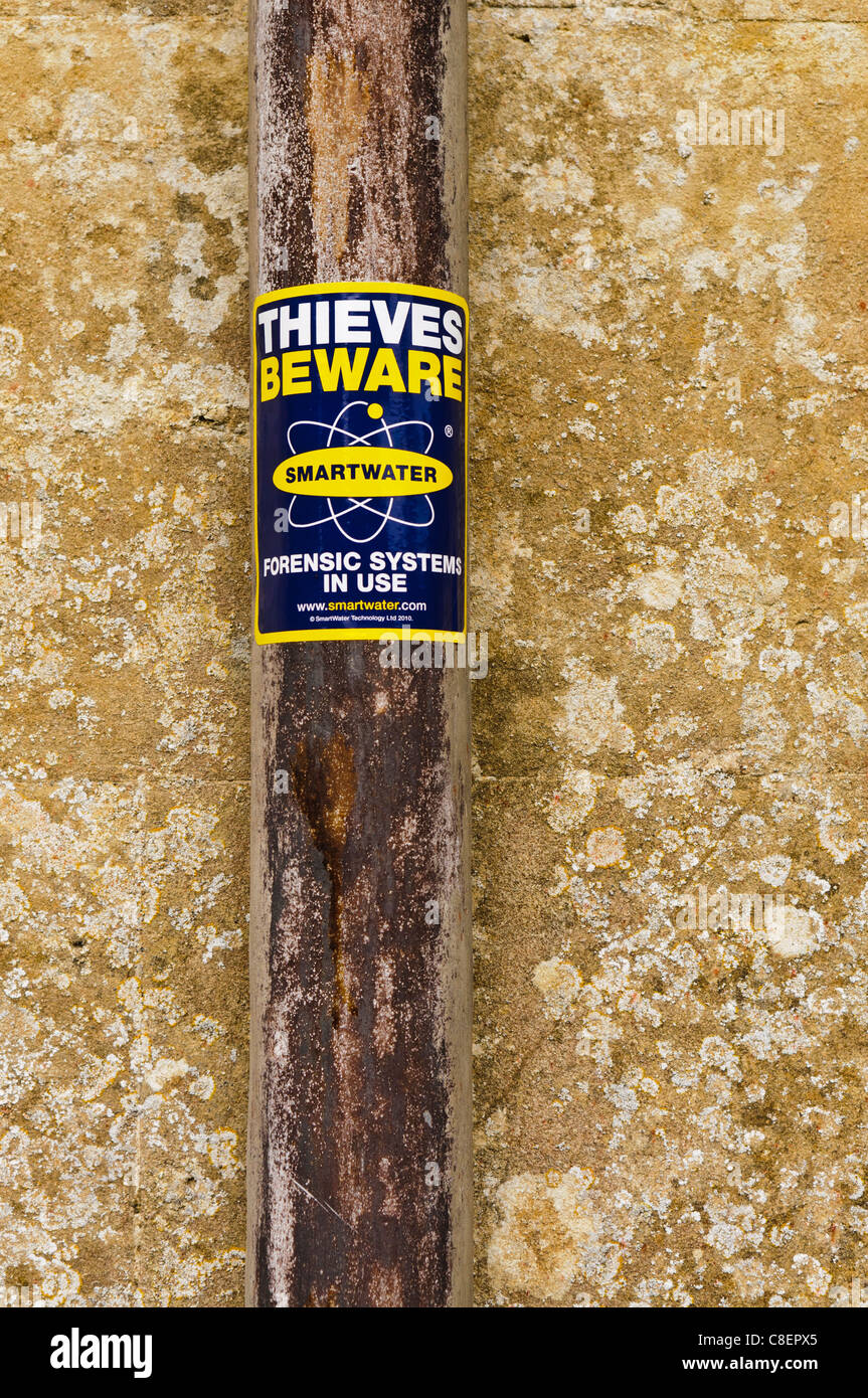 Sign on a drainpipe warning thieves that Smartwater is in use - Stock Image