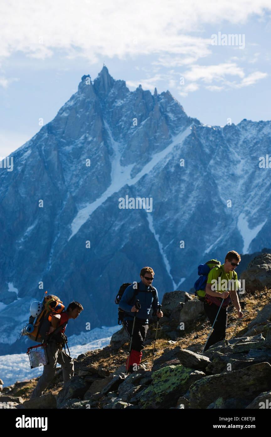 Hikers on Mont Blanc against mountain backdrop of Aiguille du Midi, Chamonix, France - Stock Image