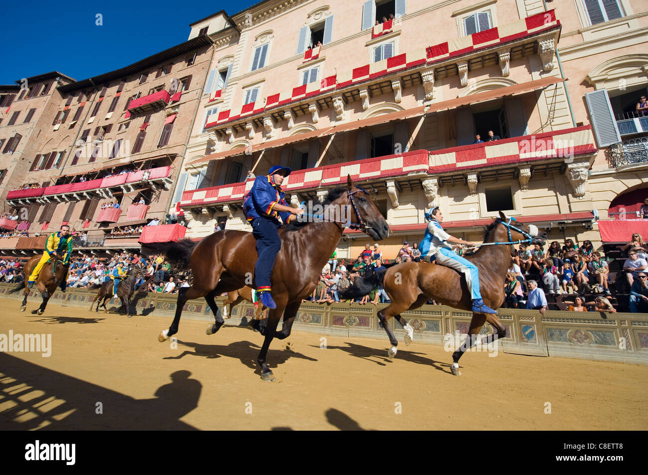Riders racing at El Palio horse race festival, Piazza del Campo, Siena, Tuscany, Italy - Stock Image