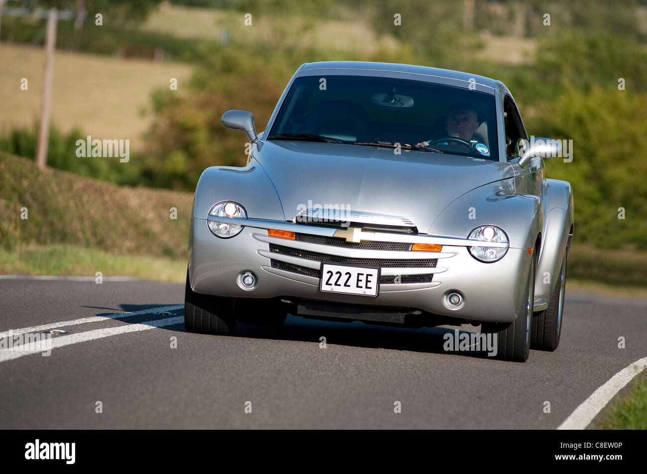 Silver Chevrolet SSR (Super Sport Roadster) being driven on a road in England. - Stock Image
