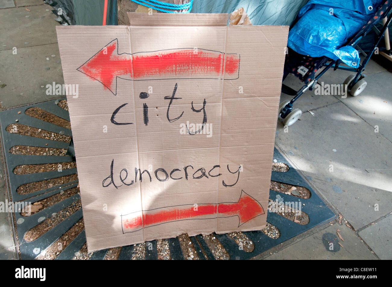 Occupy the London Stock Exchange camp  to protest at economic situation. A sign with 2 arrows, one city, one democracy - Stock Image