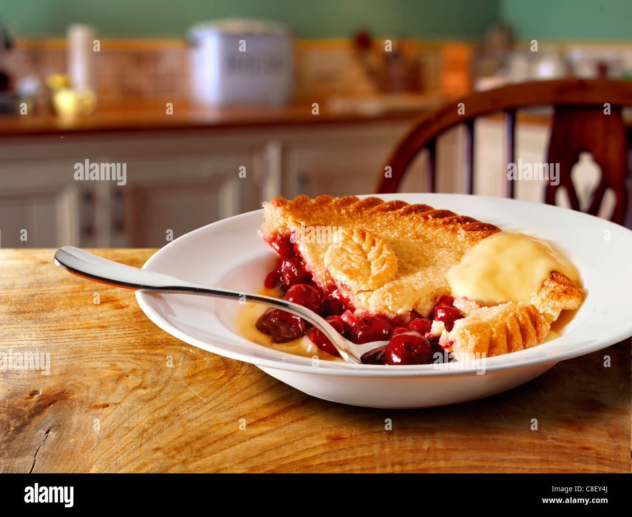 Traditional British cherry pie and custard pudding served hot in a bowl in a kitchen setting - Stock Image
