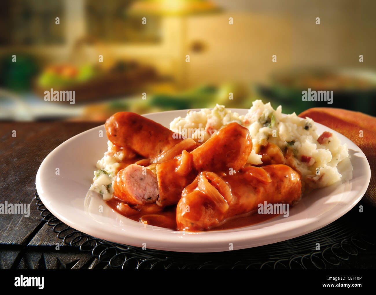 Traditional cooked Sausage and mash served on a white plate in a table setting ready to eat Stock Photo