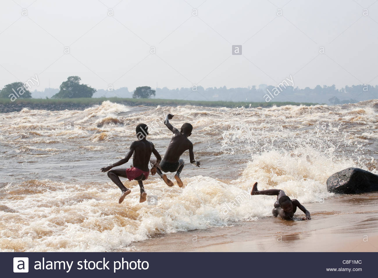 Young Congolese boys at play along the Zaire River at Kinsuka Rapids. - Stock Image